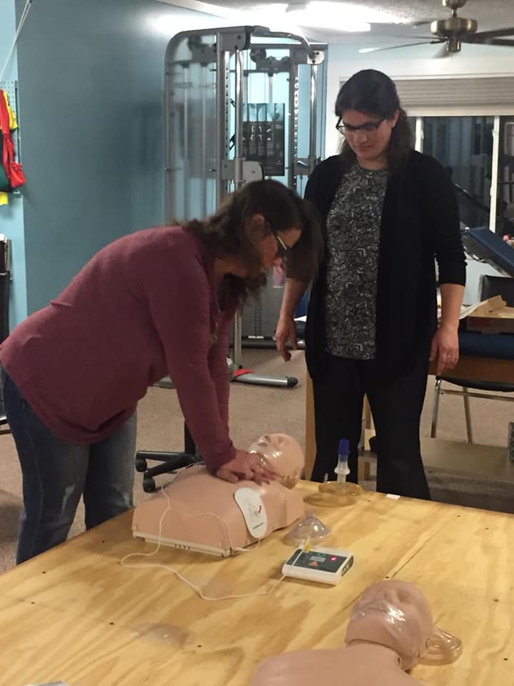 two people learning cpr at a wellness workshop
