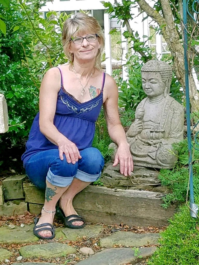leasa in blue dress sitting in garden with buddha statue